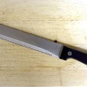 Ein Brotmesser liegt auf einem Holzbrett.